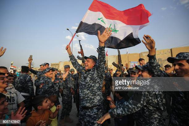 TOPSHOT Members of the Iraqi federal police dance with children and a national flag during a celebration in the Old City of Mosul where the gruelling...