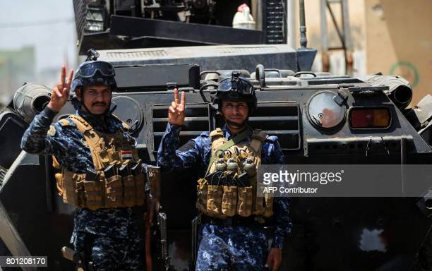 Members of the Iraqi federal police flash the victory sign by an armoured vehicle during the advance through the Old City of Mosul on June 26 as the...