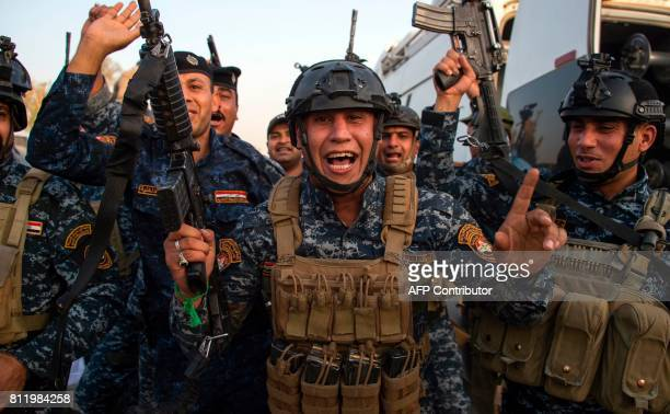 Members of the Iraqi federal police forces celebrate in the Old City of Mosul on July 10, 2017 after the government's announcement of the...