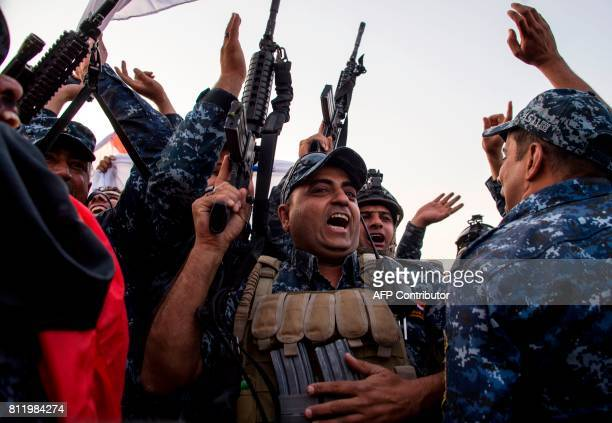 Members of the Iraqi federal police forces celebrate in the Old City of Mosul on July 10 2017 after the government's announcement of the liberation...