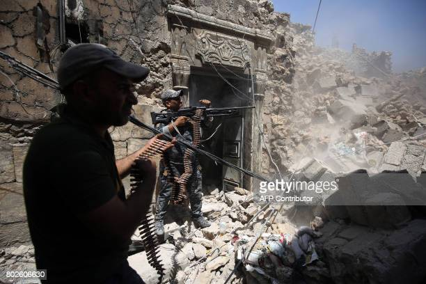 TOPSHOT Members of the Iraqi federal police hold position during an armed exchange while advancing through the Old City of Mosul on June 28 as the...