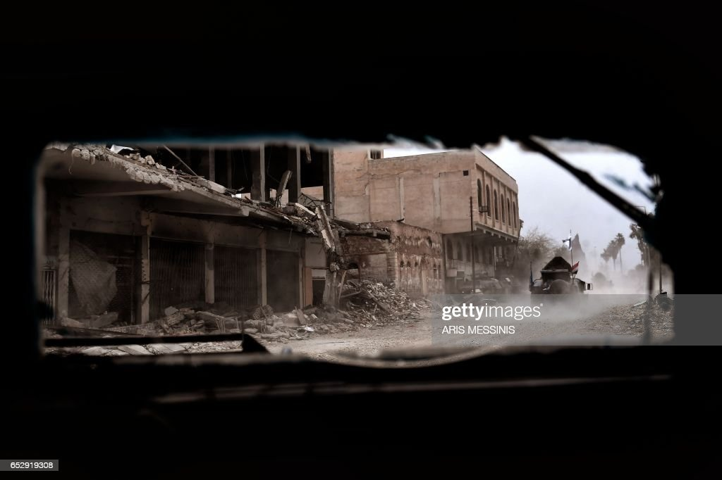 TOPSHOT - Members of the Iraqi forces advance towards the Old City in western Mosul on March 13, 2017, during an offensive to retake the city from Islamic State (IS) group fighters. /