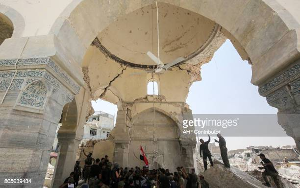 Members of the Iraqi forces along with highranking officers gather to take pictures in the remains of the Grand Mosque of AlNuri at the site where...
