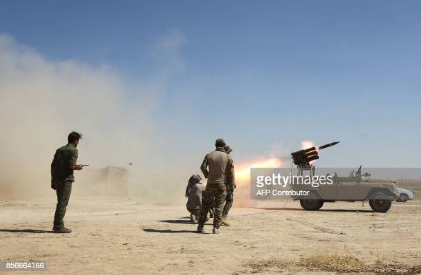 Members of the Iraqi forces and the Hashed al-Shaabi fire a rocket as they advance towards the Islamic State group's stronghold of Hawija on October...
