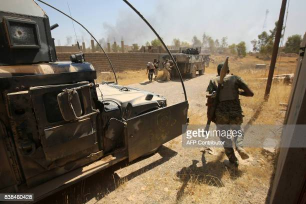 TOPSHOT Members of the Iraqi forces backed by the Hashed alShaabi advance through Tal Afar's alWahda district during an operation to retake the Iraqi...