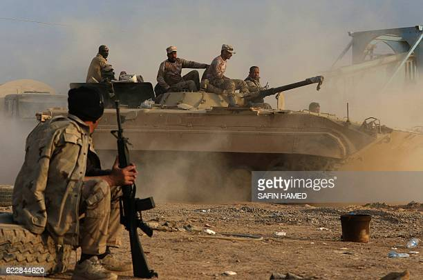 Members of the Iraqi forces drive a BMP1 infantry fighting vehicle as they hold a position in the village of Jarif some 45 kilometres south of Mosul...