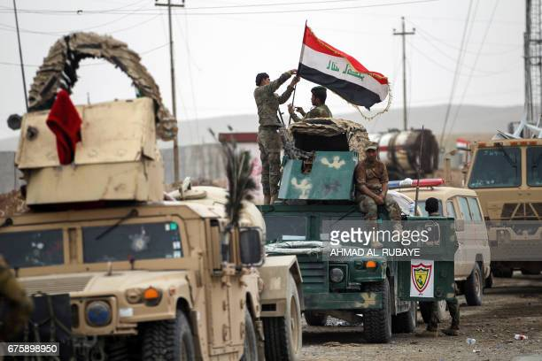 Members of the Iraqi forces fix an Iraqi flag on the turret of an armoured vehicle during a patrol in west Mosul on May 2 during the offensive to...