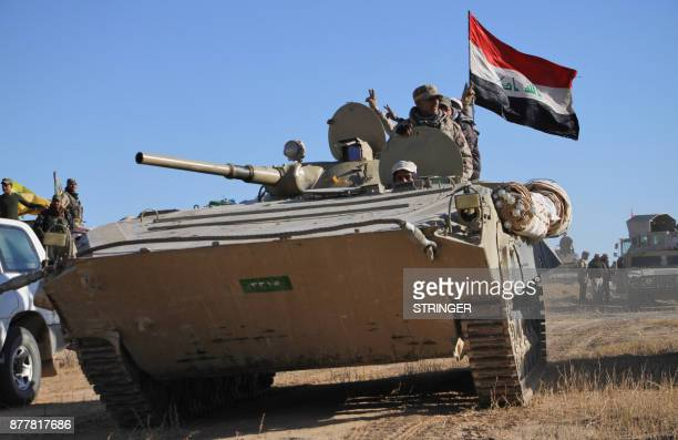 Members of the Iraqi forces flash the victory gesture from an infantry fighting vehicle as they and members of the Hashed al-Shaabi , advance in the...