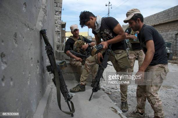 Members of the Iraqi forces get ready in Mosul's northwestern al-Haramat neighbourhood before going to the front line on May 13 during the ongoing...