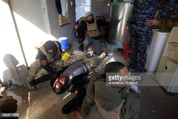 Members of the Iraqi forces give aid to a wounded comrade in Mosul's eastern AlIntisar neighbourhood on December 30 during an ongoing military...