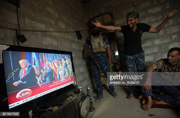 Members of the Iraqi forces react as they watch Donald Trump giving a speech after he won the US president elections in the village of Arbid on the...