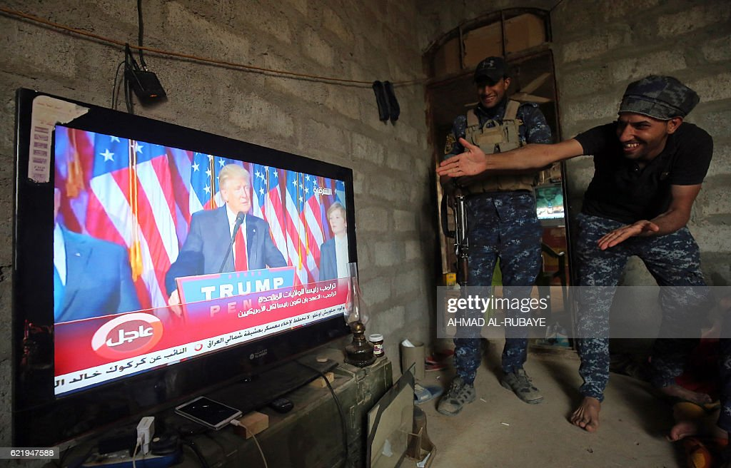 TOPSHOT - Members of the Iraqi forces react as they watch Donald Trump giving a speech after he won the US president elections in the village of Arbid on the southern outskirts of Mosul on November 9, 2016, as they rest in a house during the ongoing military operation to retake Mosul from the Islamic State (IS) group. Iraqi Prime Minister Haider al-Abadi congratulated Donald Trump on his election as president and said he hoped for continued US and international support in the war against jihadists. RUBAYE