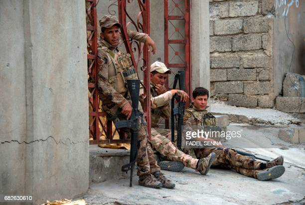 Members of the Iraqi forces rest in Mosul's northwestern al-Haramat neighbourhood before going to the front line on May 13 during the ongoing...