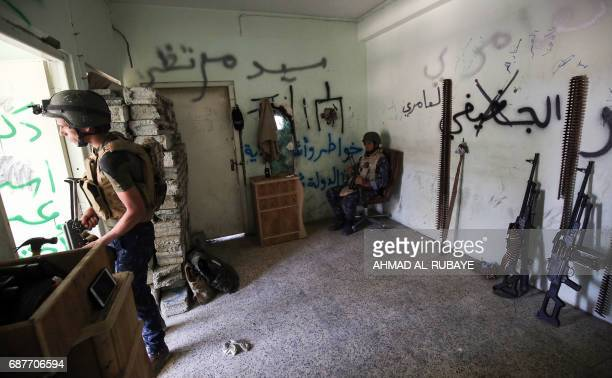 Members of the Iraqi forces stand guard in a house on the frontline in the old city of Mosul on May 24 during the ongoing offensive to retake the...