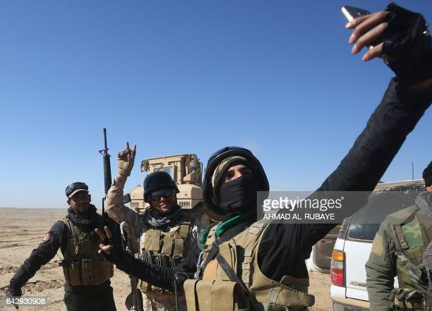 Members of the Iraqi forces, supported by the Hashed al-Shaabi paramilitaries, take a selfie as they prepare to advance towards the village of Sheikh...