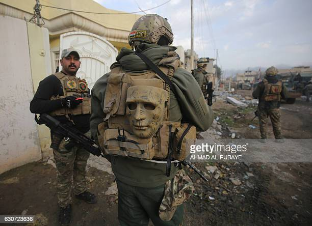 TOPSHOT Members of the Iraqi forces take position as they advance in Mosul's eastern AlIntisar neighbourhood on December 31 during an ongoing...