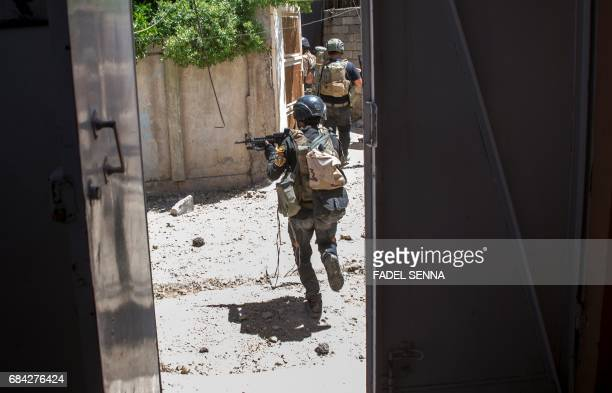TOPSHOT Members of the Iraqi forces take position in a neighbourhood of west Mosul on May 17 during an ongoing offensive to retake the area from...