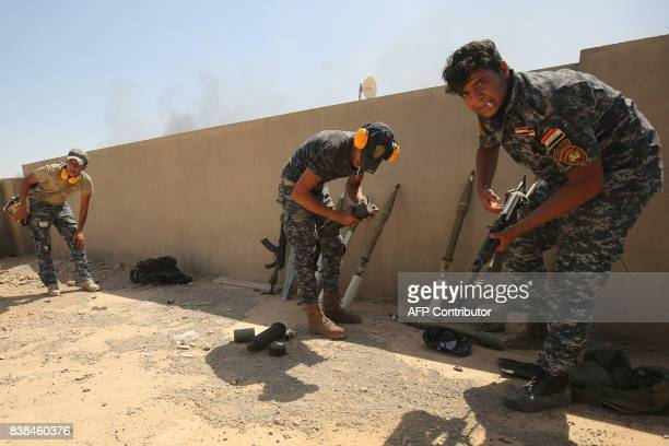 Members of the Iraqi forces take position on a roof as troops, backed by the Hashed al-Shaabi , advance through Tal Afar's al-Wahda district during...
