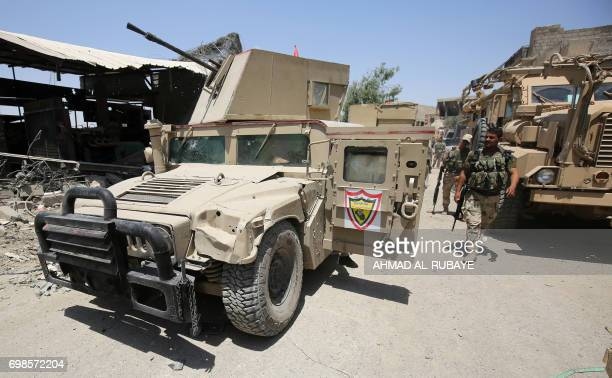 Members of the Iraqi forces walk past parked humvees and armoured vehicles during the advance towards the Old City of Mosul on June 20 2017 as the...