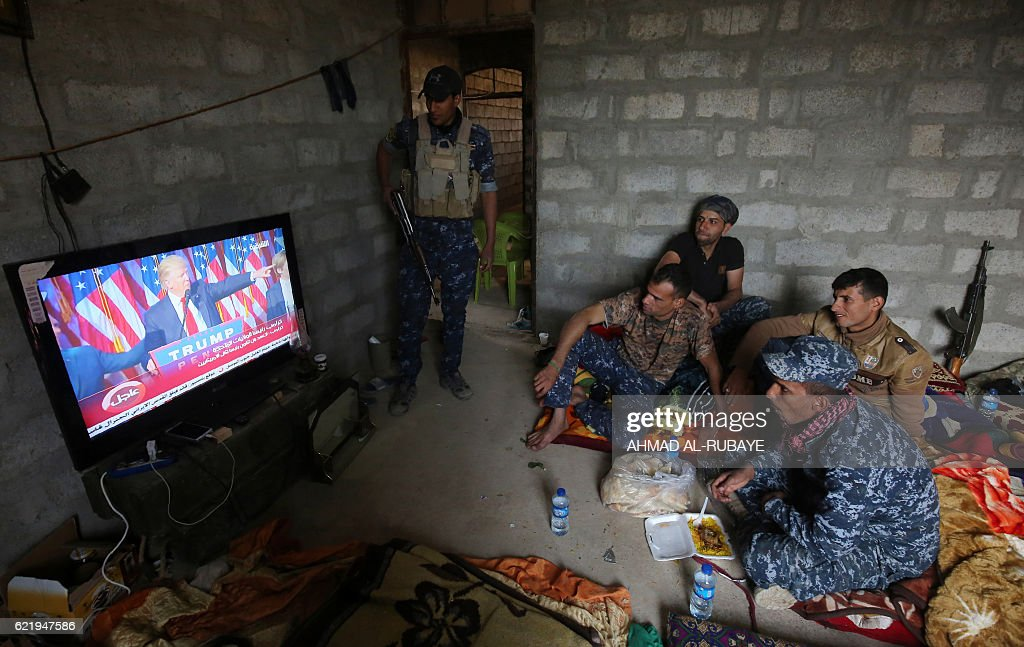 Members of the Iraqi forces watch Donald Trump giving a speech after he won the US president elections in the village of Arbid on the southern outskirts of Mosul on November 9, 2016, as they rest in a house during the ongoing military operation to retake Mosul from the Islamic State (IS) group. Iraqi Prime Minister Haider al-Abadi congratulated Donald Trump on his election as president and said he hoped for continued US and international support in the war against jihadists. RUBAYE