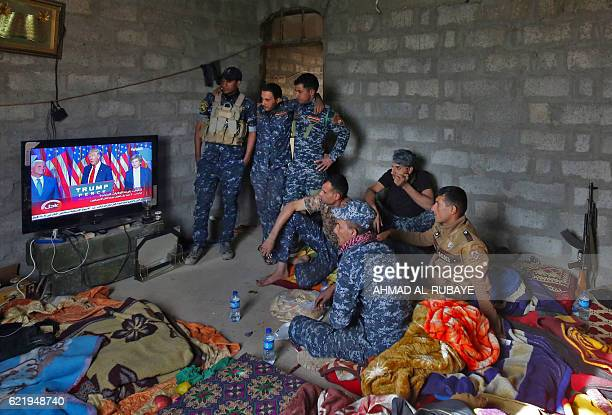 TOPSHOT Members of the Iraqi forces watch Donald Trump giving a speech after he won the US president elections in the village of Arbid on the...
