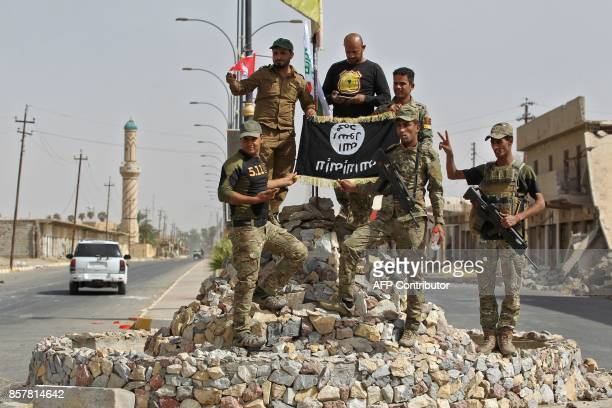 Members of the Iraqi forces which are backed by fighters from the Hashed alShaabi pose for a photograph in Hawija on October 5 after retaking the...