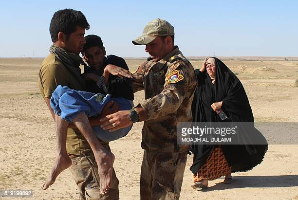 TOPSHOT Members of the Iraqi government forces carry a disabled boy as they evacuate hundreds of Iraqis from the town of Heet in Iraq's Anbar...