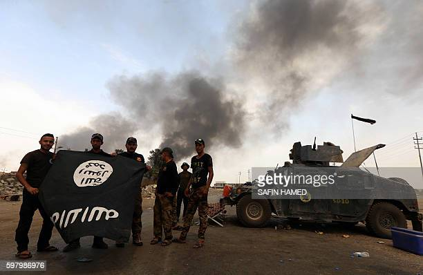 Members of the Iraqi government forces hold an Islamic State group flag upside down as smoke billows from oil wells set ablaze by IS militants before...