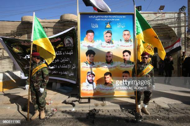 Members of the Iraqi Hezbollah Brigades part of the Hashed alShaabi paramilitary units carry flags in front of portraits of fellow members who were...