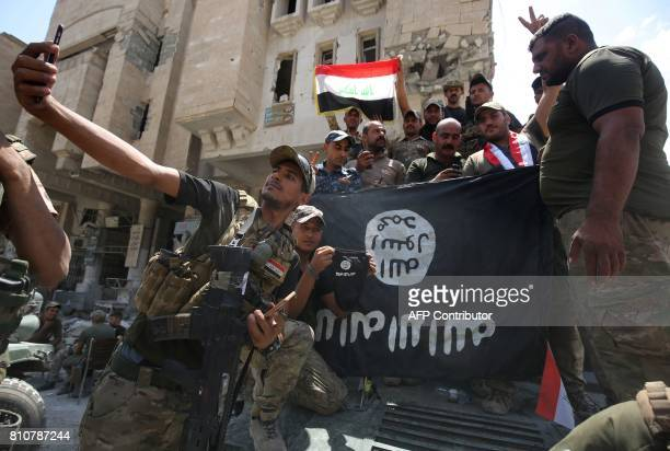 Members of the Iraqi interior ministry forces pose for a picture with an upside down Islamic State group flag in the Old City of Mosul on July 8 as...
