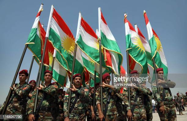 Members of the Iraqi Kurdish Peshmerga stand holding flags of Iraq's autonomous Kurdistan region a training session by German military officers...