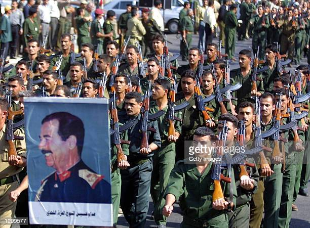 Members of the Iraqi military march with a poster of Iraqi President Saddam Hussein during a parade as the nation marks the 14th anniversary of the...
