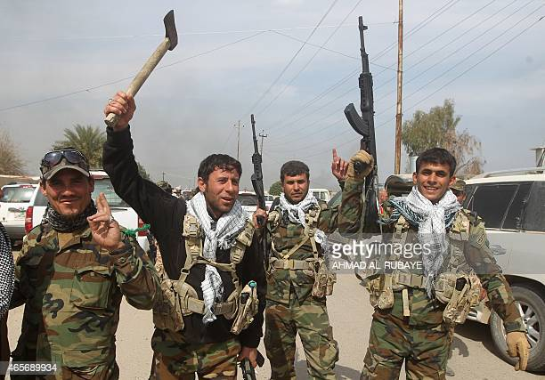 Members of the Iraqi paramilitary Popular Mobilisation units, which are dominated by Shiite militias, celebrate after regaining control of the...