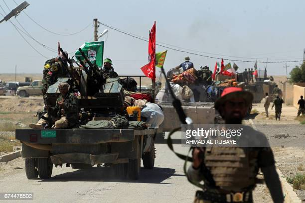Members of the Iraqi progovernment Hashed alShaabi paramilitary forces gather in a street in the modern town of Hatra near the eponymous UNESCOlisted...