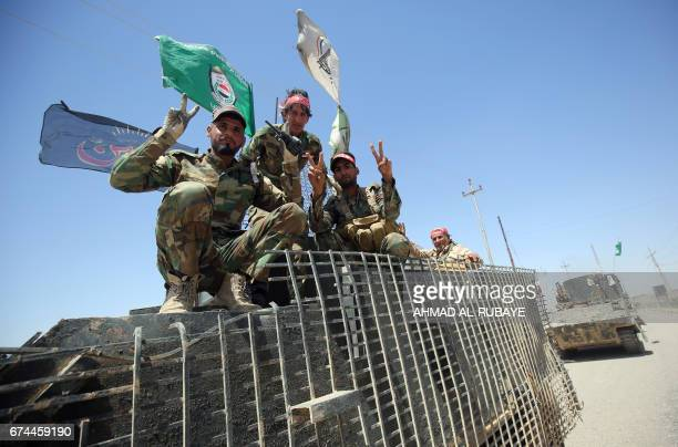 Members of the Iraqi pro-government Hashed al-Shaabi paramilitary forces gesture from the modern town of Hatra, near the eponymous UNESCO-listed...
