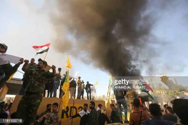 Members of the Iraqi pro-Iranian Hashed al-Shaabi group and protesters set ablaze a sentry box in front of the US embassy building in the capital...