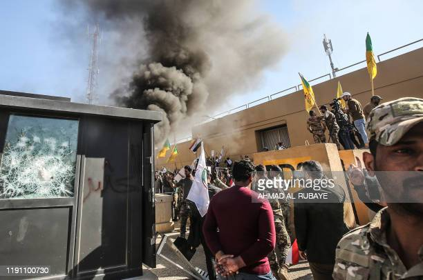 Members of the Iraqi proIranian Hashed alShaabi group and protesters set ablaze a sentry box in front of the US embassy building in the capital...