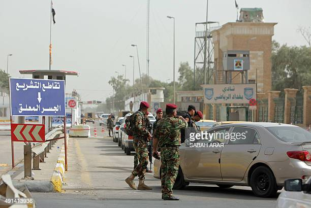 Members of the Iraqi security force stand guard as cars queue to cross into Baghdad's Green Zone on October 5 2015 after the area was opened the...