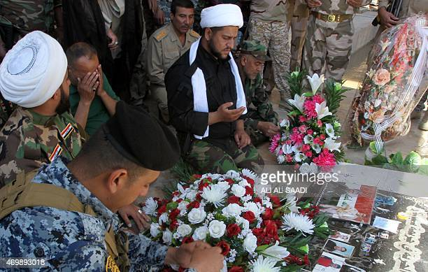 Members of the Iraqi security forces and Popular Mobilisation units pray during a memorial ceremony on the Tigris river waterfront in Tikrit on April...