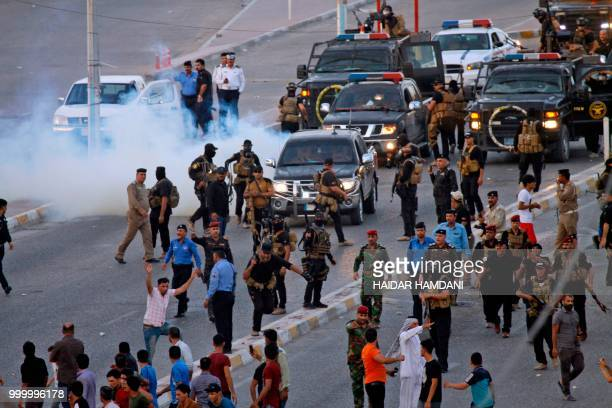 Members of the Iraqi security forces deploy during clashes with protesters in the central shrine city of Najaf on July 14 2018 Unrest in southern...