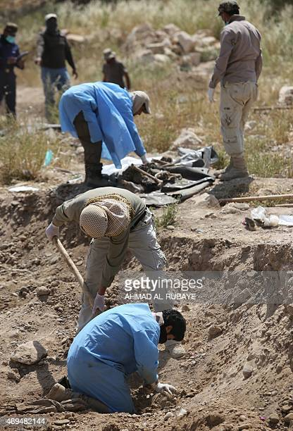 Members of the Iraqi security forces excavate a mass grave containing the remains of people believed to have been slain by jihadists of the Islamic...