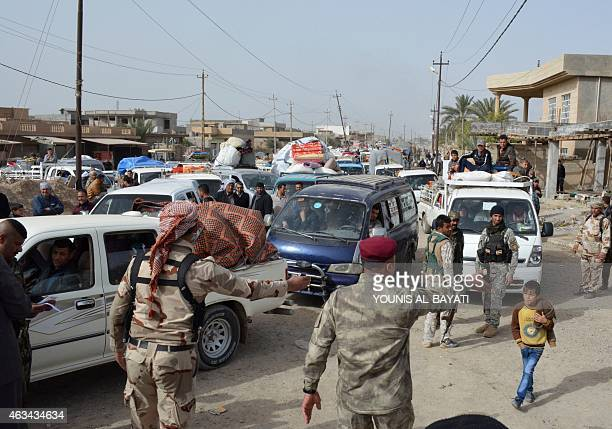 Members of the Iraqi security forces give directions and cehck documents as Iraqis return to the village of AlMansuriya 65 kilometres northeast of...