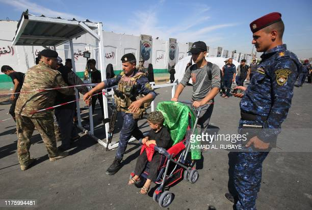 Members of the Iraqi security forces handsearch Shiite Muslim pilgrims as they take part in a procession from Baghdad to the shrine of Imam Hussein...