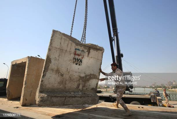 Members of the Iraqi security forces remove concrete blocks on Baghdad's Sinek bridge which was reopened on October 27, 2020 after being closed last...