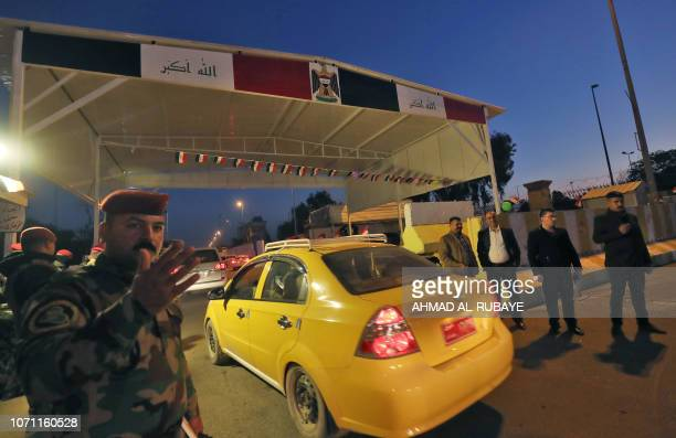 Members of the Iraqi security forces stand at a checkpoint as traffic passes by in the capital Baghdad's highsecurity Green Zone where key government...