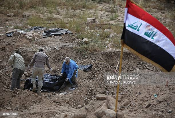 Members of the Iraqi security forces wearing protective clothes inspect a mass grave containing the remains of people believed to have been slain by...