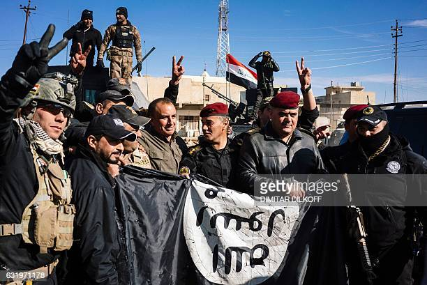 Members of the Iraqi special forces Counter Terrorism Service hold an Islamic State group flag as they celebrate in their military base in the town...