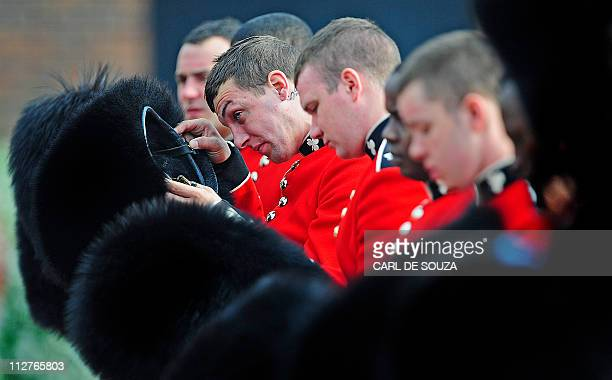Members of the Irish Guards regiment take off their bearskin hats after an official uniform inspection at Victoria barracks in Windsor on April 21...