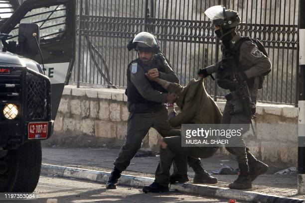 Members of the Israeli border police arrest a Palestinian demonstrator during clashes following a protest in the West Bank city of Bethlehem on...