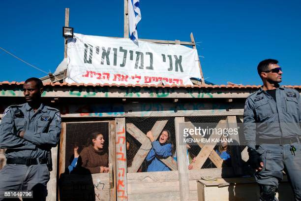 Members of the Israeli border police stand next to Jewish settlers who barricaded themselves inside an illegallybuilt structure on private...
